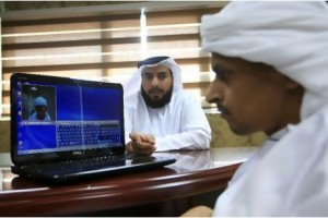 Hashim Abdullah Al Musaabi, left, of SmartSoft, the firm that invented the iMouse, explains to Mohammed Al Tamimi how to operate the mouse with a wink.  Photo credit: The National, http://www.thenational.ae