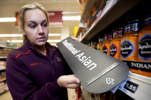 Lady at Sainsbury's store showing Braille signage exemplar.