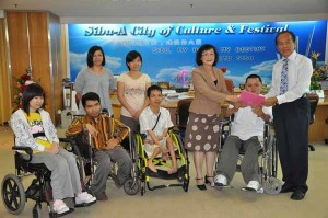 Wong hands over the letter to SMC chairman Tiong Thai King (right) at his office while wheelchair users and others look on