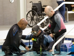 Edward James (left) and Duane Blau (right) help disabled Air Force veteran Keenan Lee, of Mesa, into the pool at Virginia G. Piper Sports & Fitness Center in Phoenix. (Photo credit: Cheryl Evans/The Arizona Republic)