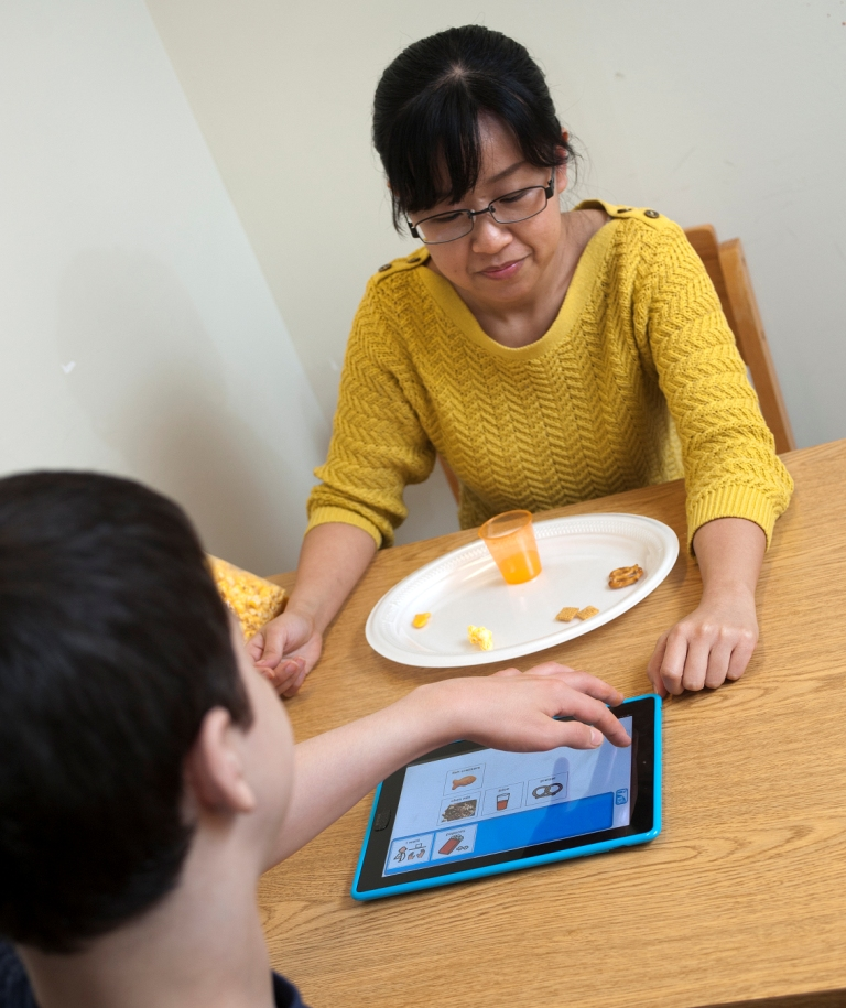 Doctoral student Ming Hsu works with Quentin Travers, 12, in the Purdue University Speech-Language Clinic. Quentin uses the iPad SPEAKall! app to ask for the items on the plate. (Photo credit: Purdue University/Mark Simons)