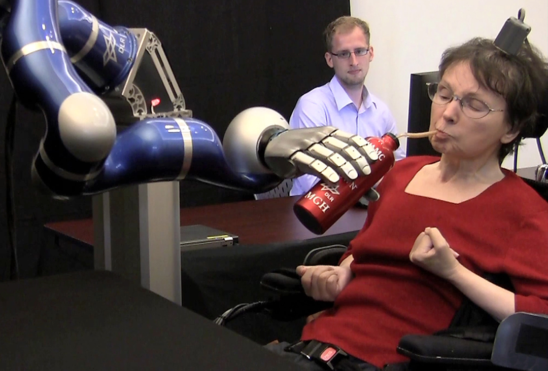 Using a robot arm, 'Cathy' was able to lift a bottle and drink for the first time in 15 years. (Photo credit:  Braingate2.org)