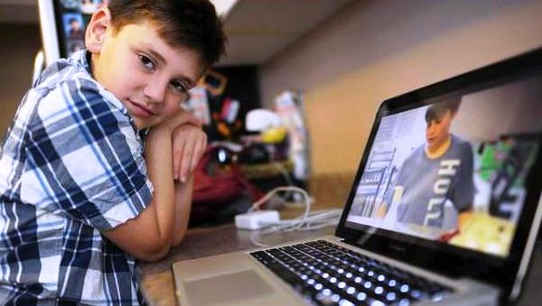 Ten year old Jordan Hilkowitz is photographed in the kitchen with a laptop showing his website on science experiments on June 8 2012. (Photo Credit: Fred Lum/The Globe and Mail)