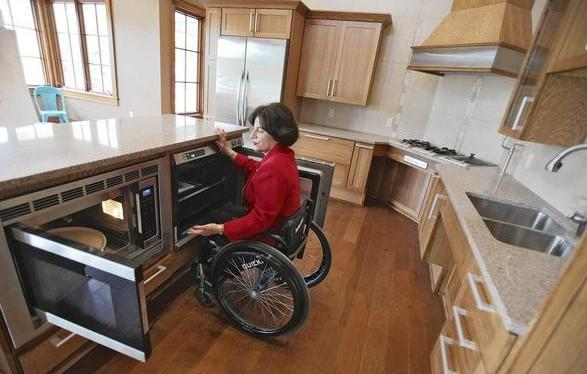 Rosemarie Rossetti shows off her new kitchen, which includes three staggered levels of countertops, a lower microwave and oven, and a roll-up stovetop. Her new home is called the Universal Design Living Laboratory. (Photo credit: Courtney Hergesheimer, Columbus Dispatch)