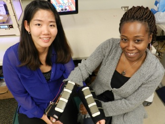 Ayanna Howard (right), professor of electrical and computer engineering, and graduate student Hae Won Park (left) have created Access4Kids, a wireless input device that uses a sensor system to translate physical movements into fine-motor gestures to control a tablet. (Photo credit: Georgia Tech)