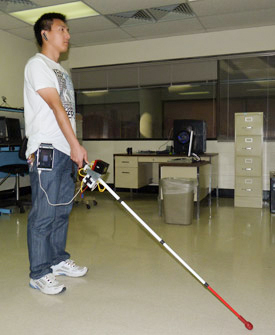A person holding a prototype co-robotic cane for people with vision disabilities. Photo Cang Ye, Ph.D., University of Arkansas at Little Rocky