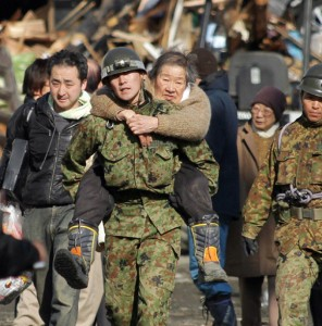 A soldier carries an elderly woman on his back as people are evacuated to a shelter at Kesennuma city in Miyagi prefecture, Japan. (Photo: Jiji Press/AFP/Getty)