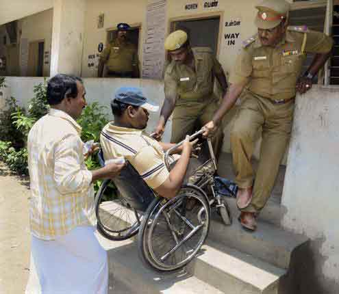 Policemen help a voter with disability at a polling booth in Virugambakkam. Photo: S.S.Kumar