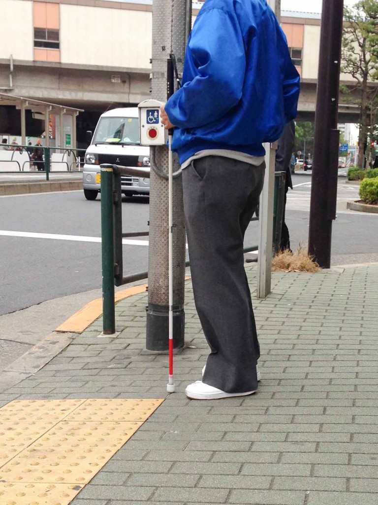 Person with vision disability waiting to cross road