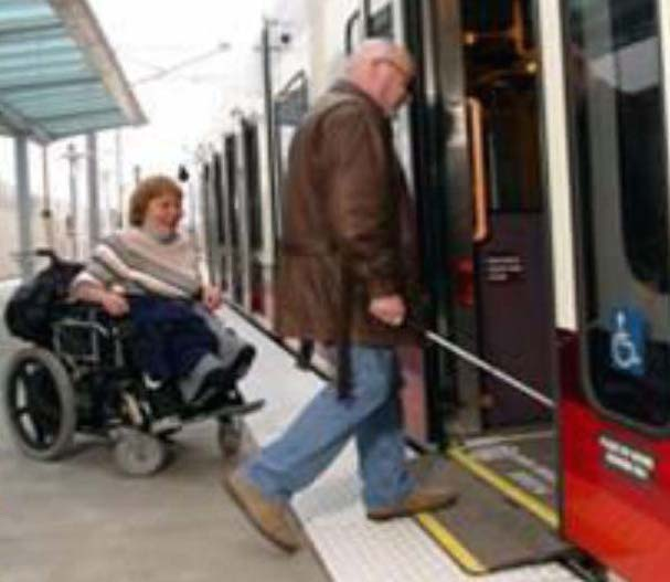 A transit train car that is accessible for all users and identified with the International symbol of accessibility, being boarded by a man walking and a women in a power wheelchair.