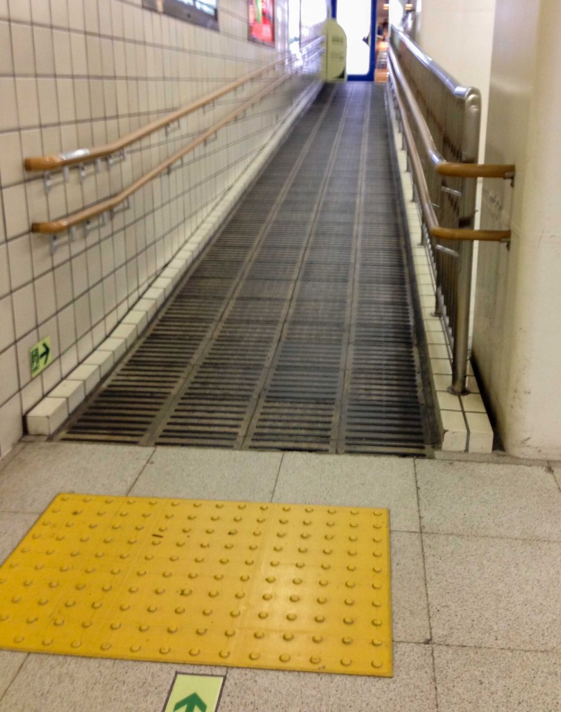 Ramp with tactile warning strips and handrails