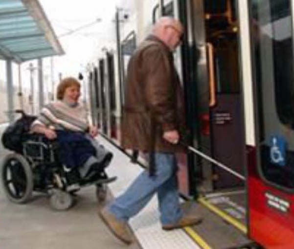 A women in a power wheelchair; photo of a woman being assisted by a service dog boarding a transit train car at an accessible station.