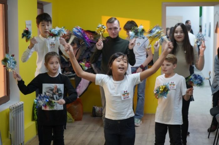 Children with disabilities dancing with pom poms in school