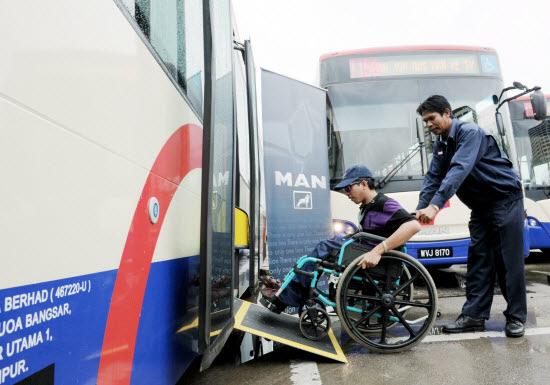 Rapid KL bus driver Azmi Salleh helping Mohd Ihsan Abdul Karim board a bus. Photo Credit: BERNAMA