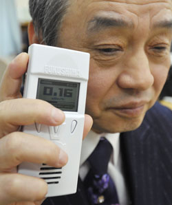 A man holds a Geiger Fukushima, a radiation detector developed for blind people, in the city of Fukushima. ( Credit: Japan Times )