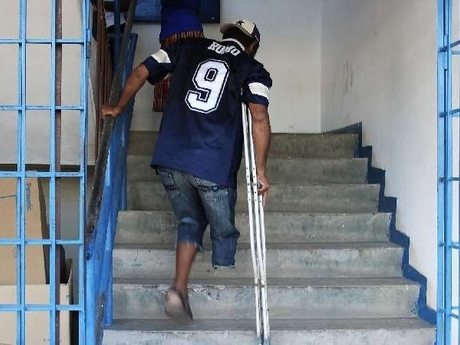 A person with disabilities climbing the first of at least three flights of stairs to access the polling station at José Martí Technical High School in St Catherine Eastern. (Photo credit: Tyrone Reid/jamaica-gleaner.com)