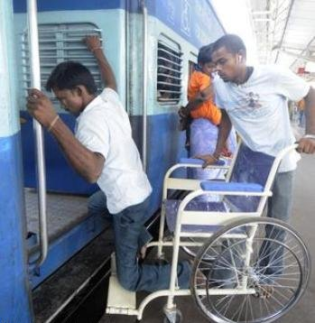A wheelchair user being assisted to board a train at Egmore railway station. (Photo credit: The Hindu)