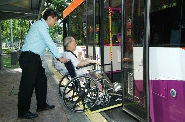 A bus driver helping a wheelchair user to board accessible bus. (Photo credit: SBS Transit)
