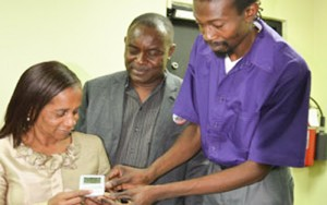 Senior Telecommunications Engineer at the Office of Disaster Preparedness and Emergency Management (ODPEM), Ruel Corniffe (right), shows Executive Director of the Combined Disabilities Association (CDA), Gloria Goffe (left), how to operate a special alert receiver. This is one of the devices to be utilized under a pilot project for the implementation of an early warning system to alert persons with disabilities of Portmore, St. Catherine of impending disaster. Photo: JIS