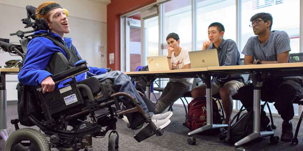 Zach Crighton, a 17-year-old high school student with cerebral palsy, meets with students in the Compassionate Design course taught by lecturer John Moalli. The students are hoping they can make improvements to Crighton's wheelchair and communication tools. (Image credit: L.A. Cicero)