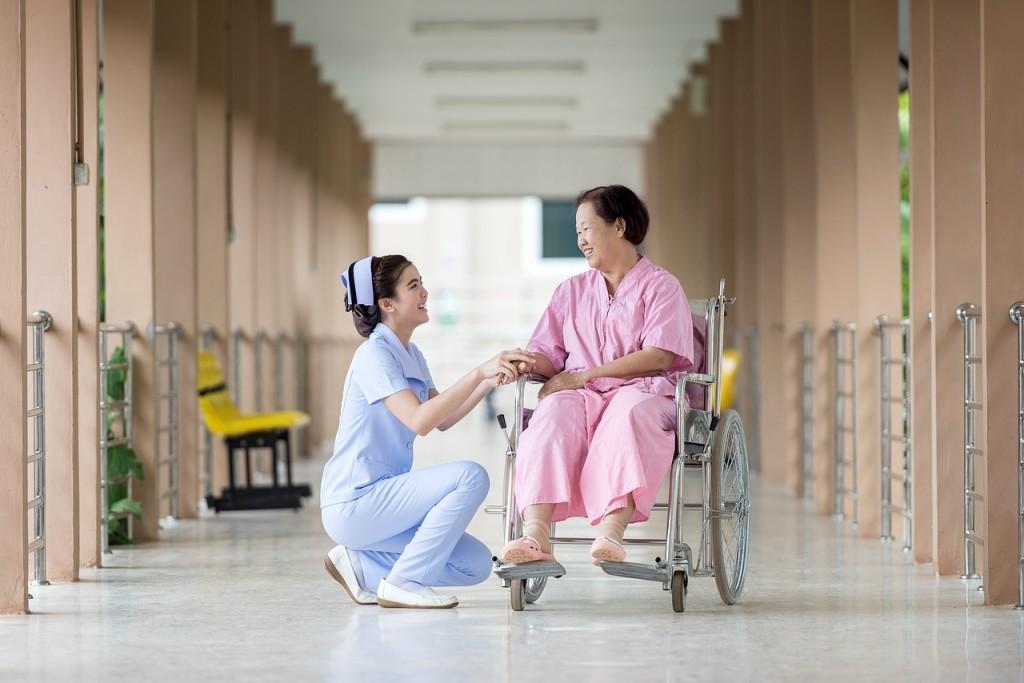 Senior female woman in wheelchair sitting in hospital corridor with female nurse