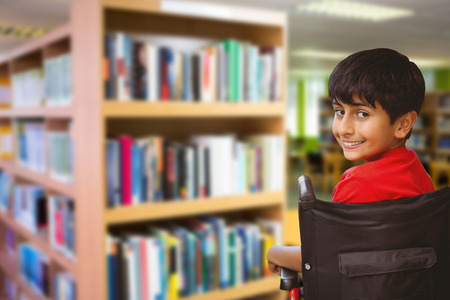 Boy sitting in wheelchair in school against volumes of books on bookshelf in library.