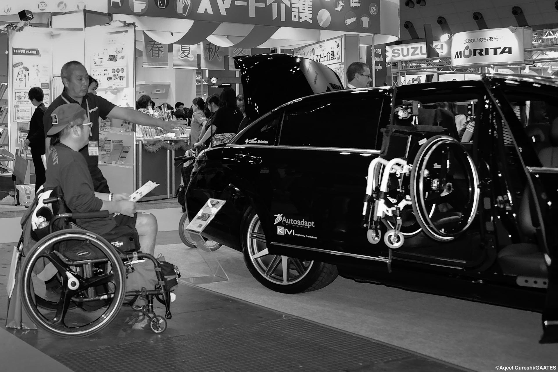 Man in a wheelchair next to an accessible car