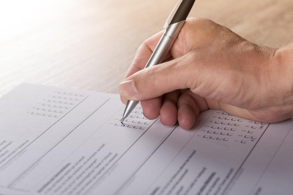 Close-up of Businessman Filling Survey Form
