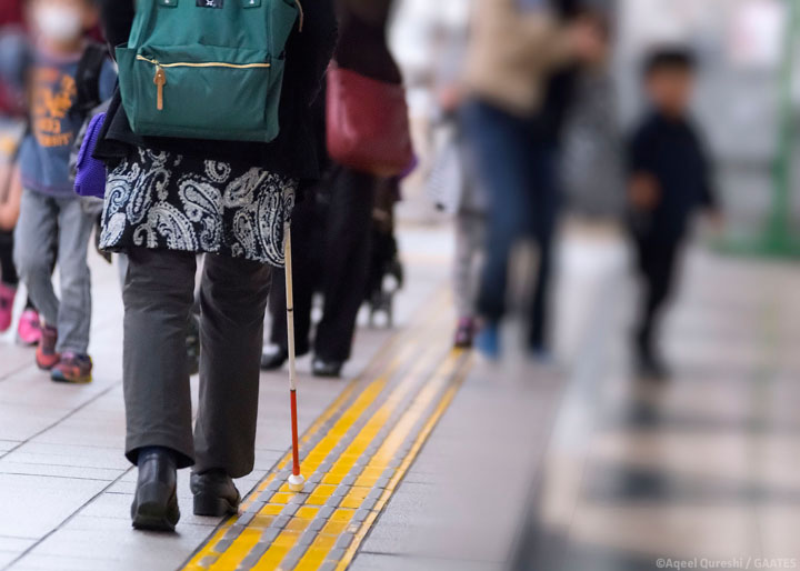 Woman who is blind with a cane walking at a subway station