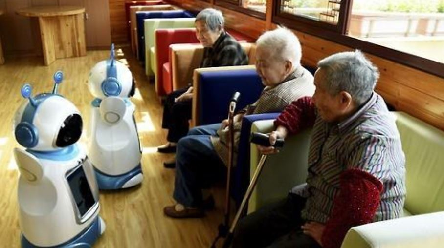 Three elderly people sitting on sofa with two robots