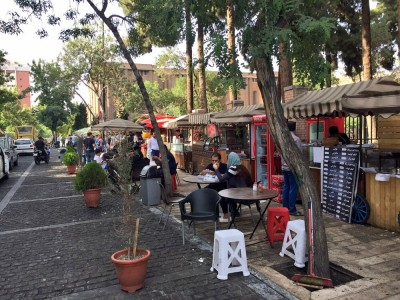 Street view with people sitting on tables on the side walk
