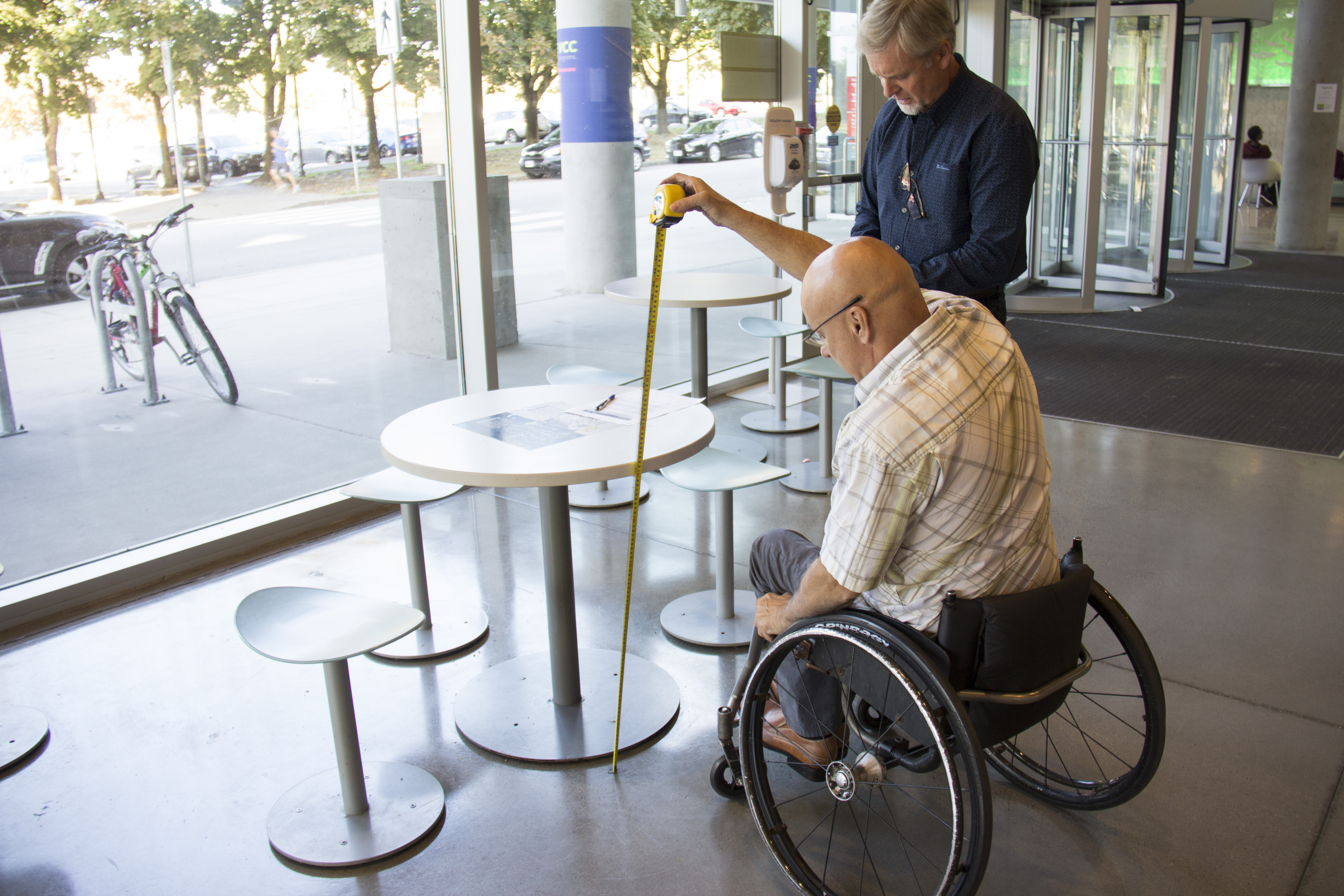 Man in wheelchair measures height of table