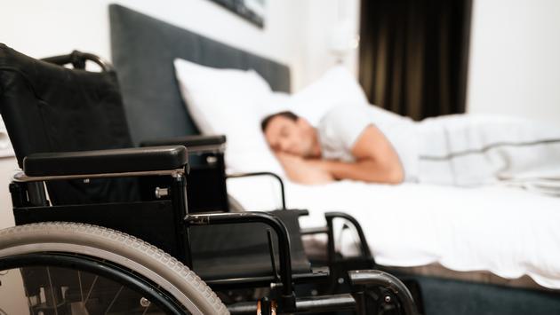 Wheelchair-user sleeping in a hotel room.
