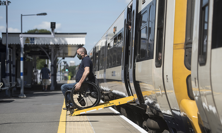 Person on a wheelchair getting down a train ramp