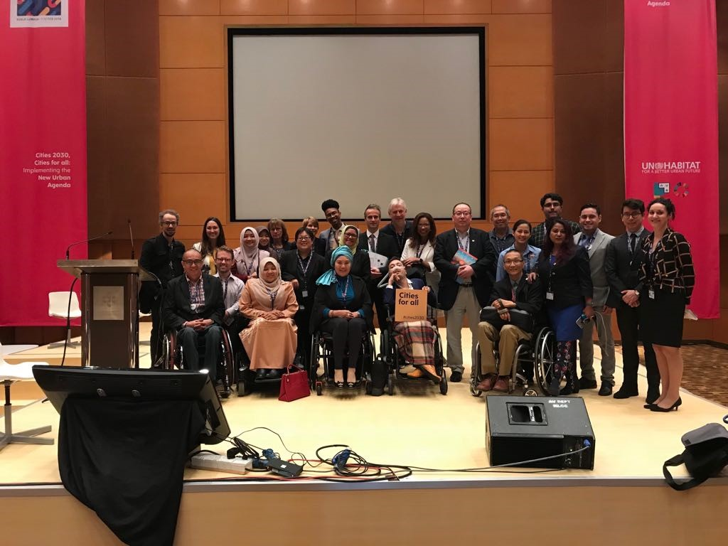 Photo of Disability advocates and Allies at the World Urban Forum holding a sign that says Cities for All