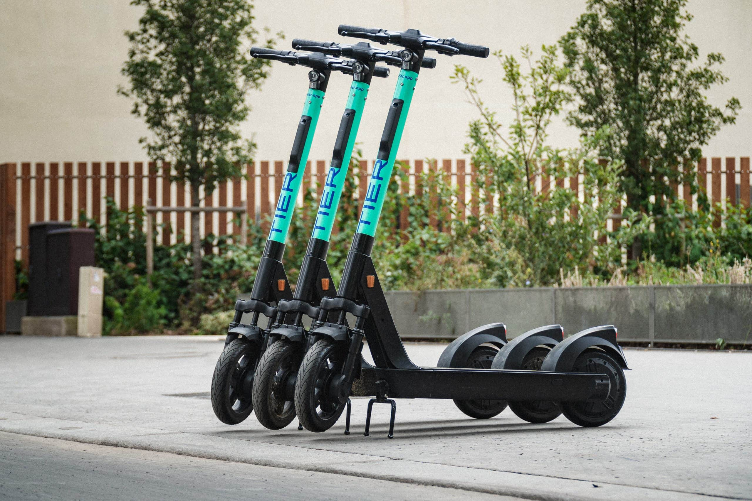 image of three e-scooters parked on the sidewalk