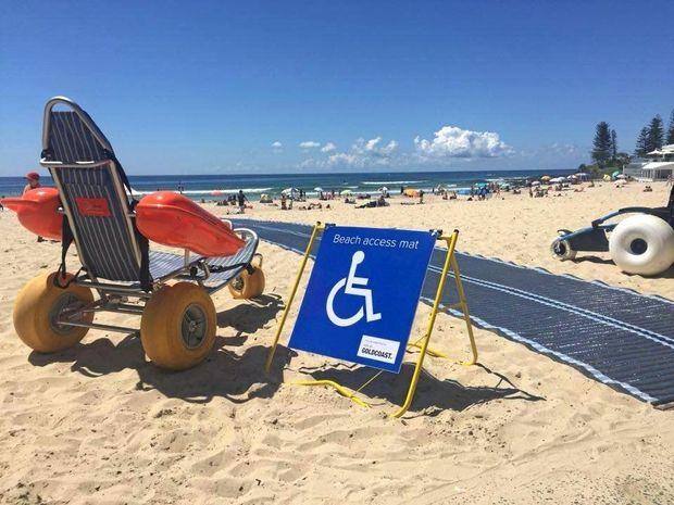 Floating wheelchair on a beach next to a sign indicating the adjacent beach access mat