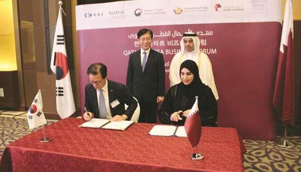 two people seated on a table and signing agreements Two people standing behind them on a stage.