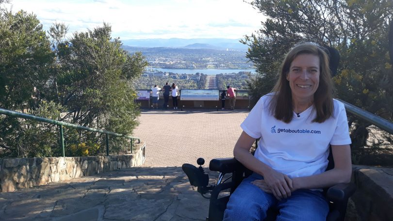 Woman in a white tee in a wheelchair posing for the camera