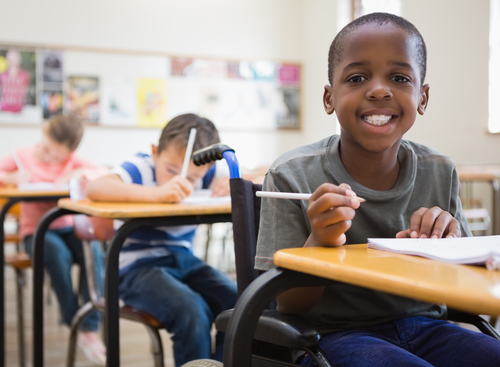 Student with disability smiling at camera in classroom at the elementary school