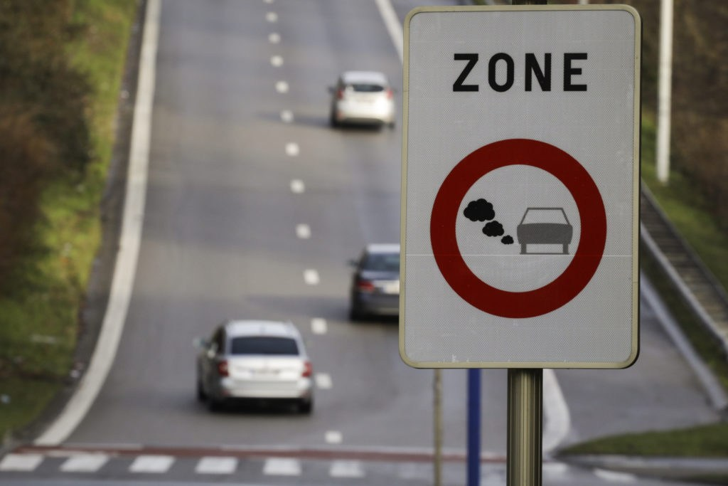 Image of a road with cars and a traffic sign board with text zone written on it.