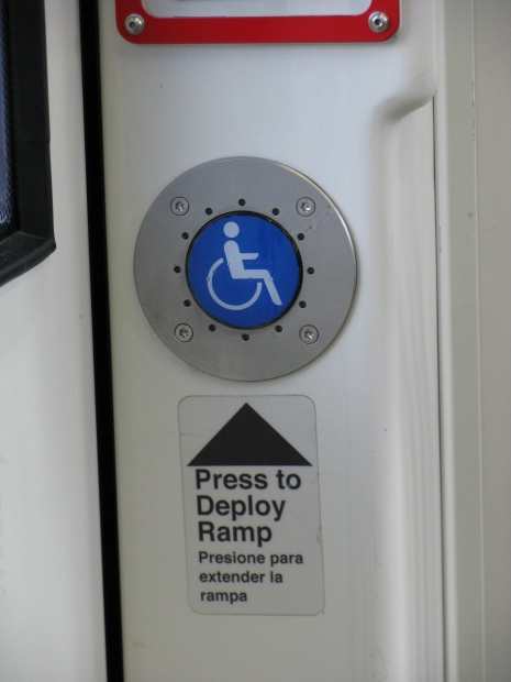 Photo of wheelchair sign with instructions to deploy the ramp