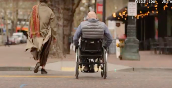 A lady walking with a man in a wheelchair in the city