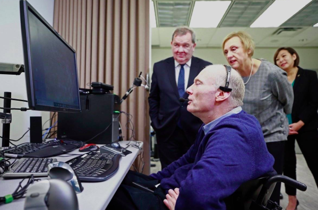 An elderly person on the computer with two persons standing beside him.
