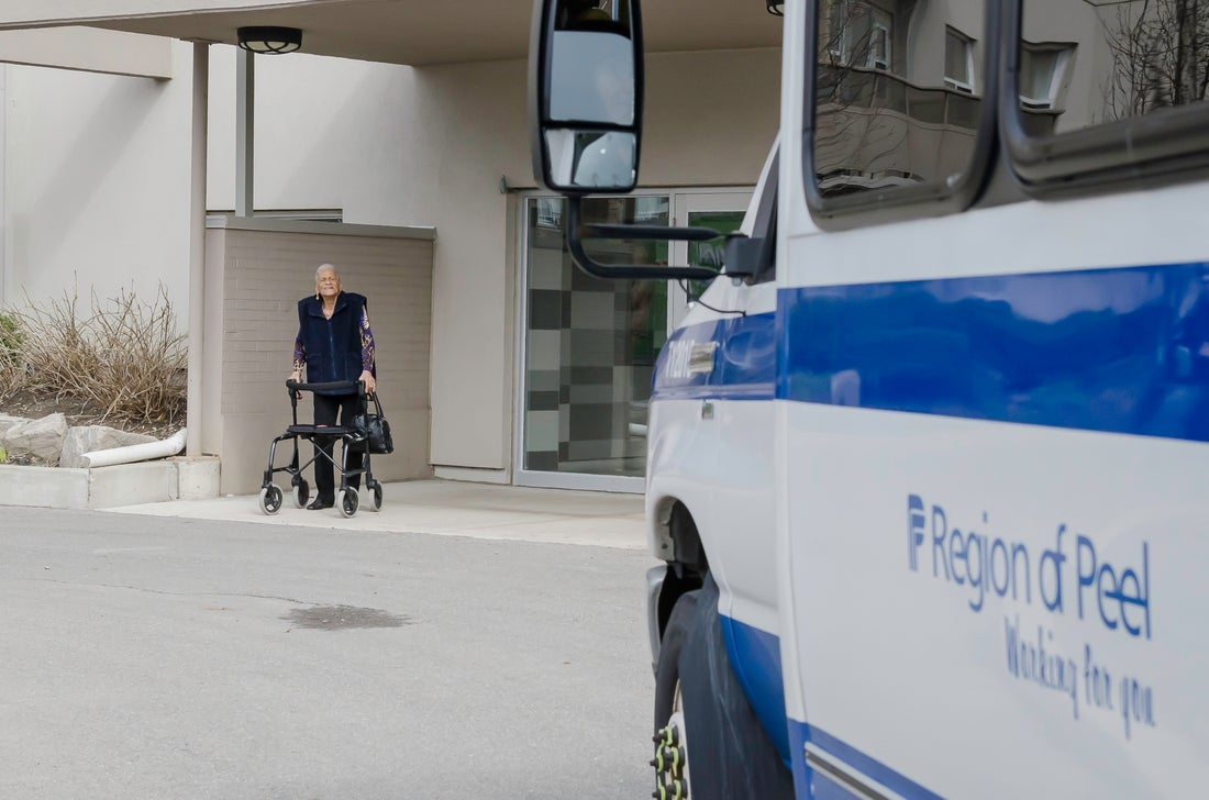 A bus of the Region of Peel with a woman with physical impairments standing near it.