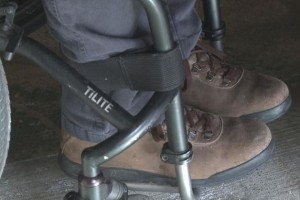 Close-up view of a person's feet in footrest of wheelchair