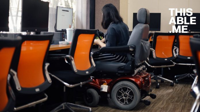 Woman seated on a wheelchair using a computer with her back towards camera.