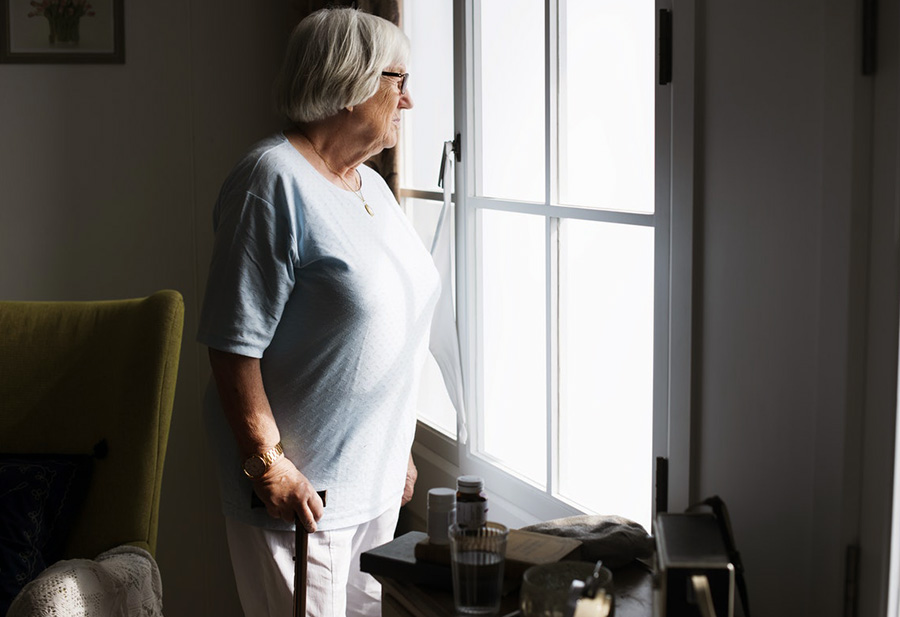 Older person looking out of the window