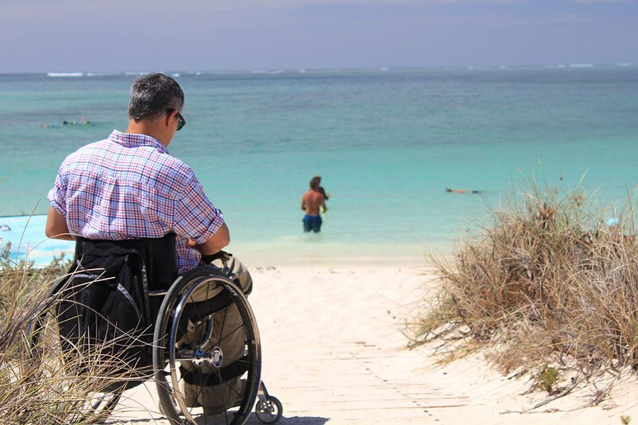 person in a wheelchair on a beach facing the sea