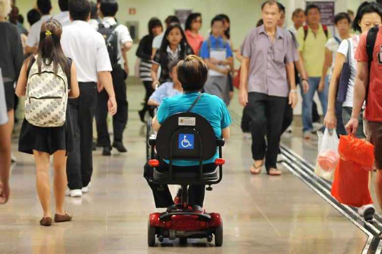 A person in a wheelchair in a public space with back towards camera.